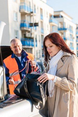 Woman searching her purse mechanic fixing car