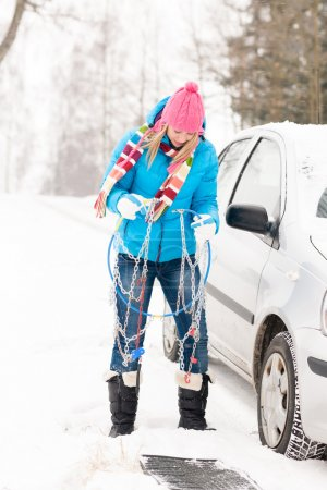 Woman having problems with car snow chains