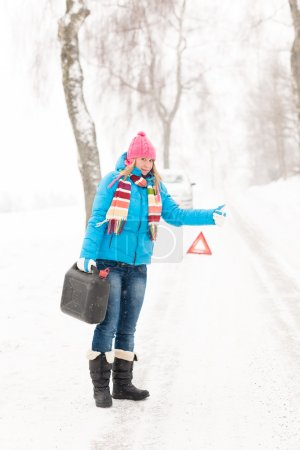 Woman hitchhiking on road snow gas can