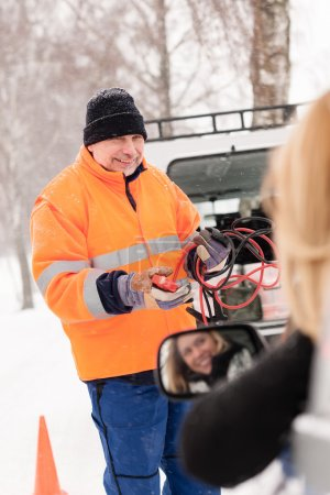Man help woman broken car starting cables