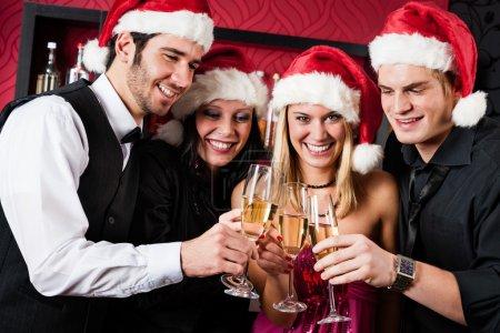 Photo pour Noël grillage parti joyeux jeunes amis au champagne au bar - image libre de droit