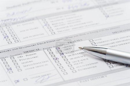 Photo pour Remplissage plume document formulaire médical d'urgence sur gros plan graphique - image libre de droit
