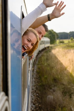 Couple screaming out train window waving happy