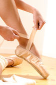Ballet dancer tying slippers around her ankle