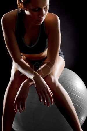 Thoughtful young woman relaxing on fitness ball