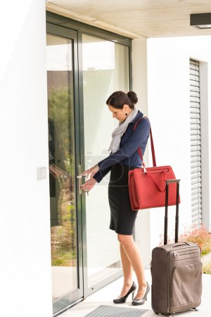 Young businesswoman locking door traveling luggage leaving