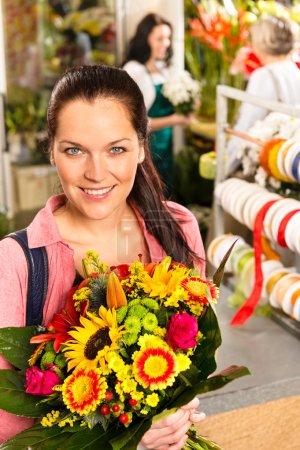 Smiling young florist woman colorful bouquet shop