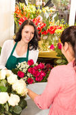 client de fleuriste heureux faisant roses bouquet femmes