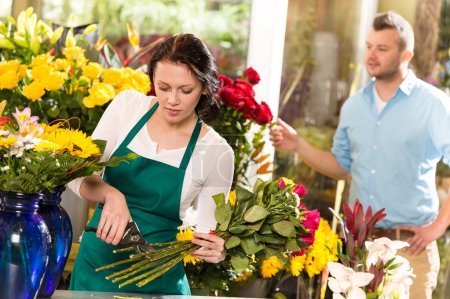 Woman florist cutting flowers shop bouquet man