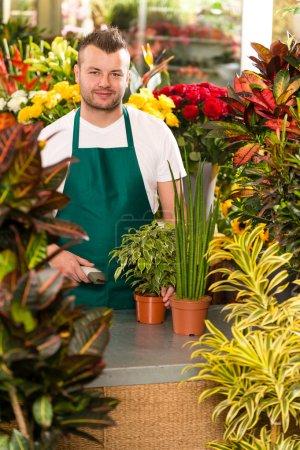 Young man scanning barcode flower shop gardening