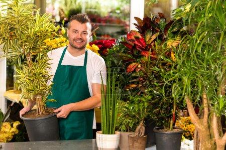 Foto de Flor de planta en maceta macho dependienta trabajando sonriendo - Imagen libre de derechos