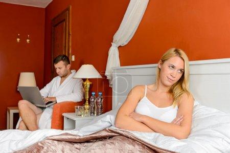 Upset girl sitting bed after fight boyfriend