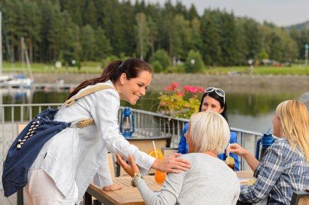 Woman arriving outdoor restaurant terrace friends