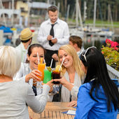 Women celebrating with cocktails at restaurant