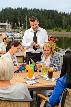Waiter taking orders sidewalk bar from women