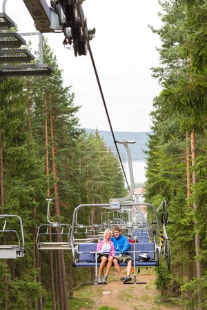Young couple sitting on chair lift landscape