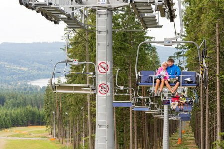 Cuddling couple going through pinewood chair lift