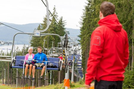 Young couple enjoying chair lift in wood