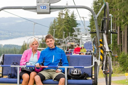 Chair lift going through forest couple sitting