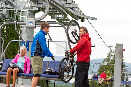 Man helping couple holding bicycle chair lift