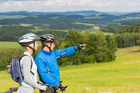 Pointing cyclists couple on summer weekend nature