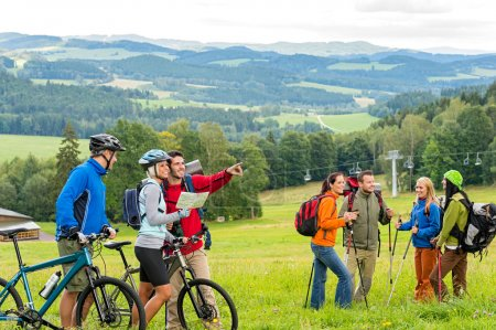 Hikers helping cyclists following track nature landscape