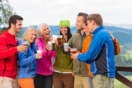 Happy friends clinking glasses drinking beer outdoors