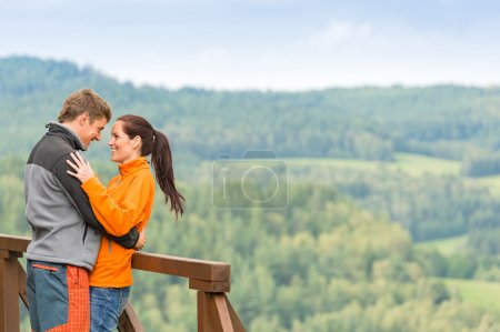 Smiling couple hugging outdoors nature background