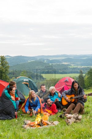 Photo for Group of friends sitting beside tents, campfire girl playing guitar - Royalty Free Image