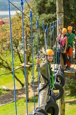 Foto de Jóvenes amigos divirtiéndose en el parque de aventura en cascos - Imagen libre de derechos