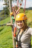Woman with helmet smiling in adventure park