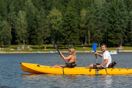 On pond young couple sitting in kayak