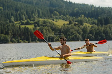 Kayaking sporty men on river sunshine
