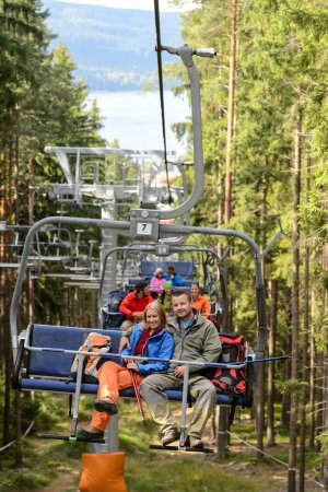 Young couple sitting on chairlift forest