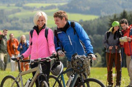 Photo pour Couple cycliste joyeux avec VTT campagne relaxante - image libre de droit