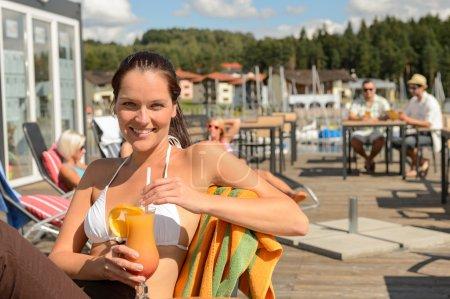 Woman drinking cocktail at beach bar