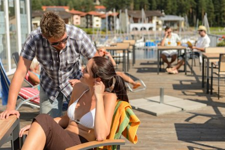 Talking young couple at beach bar