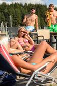 Women sunbathing on deckchair guys drinking beer