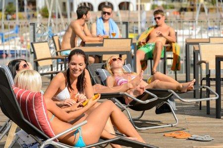 Chatting girls lying on deckchair sunbathing