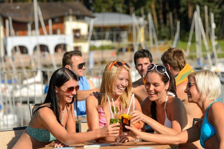 Beautiful women in bikinis toasting with cocktails