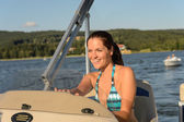 Cheerful woman navigating powerboat in summer