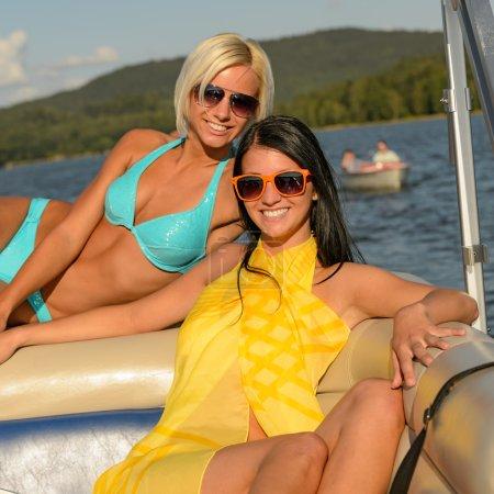 Young smiling women sunbathing on boat