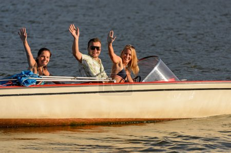 Young waving from motorboat