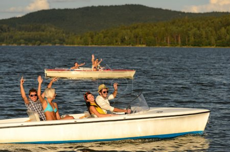 Group of friends racing with motorboats