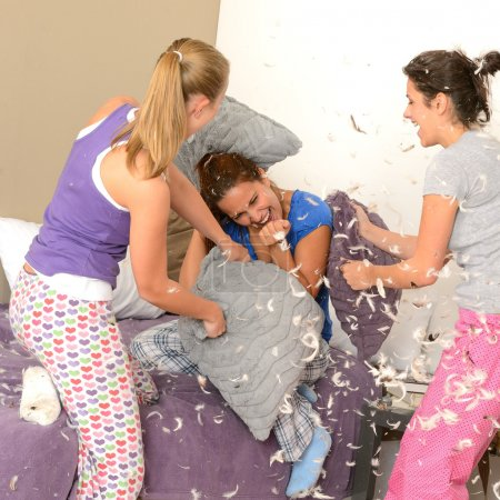 Teenager girls pillow fighting in bedroom