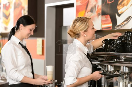 Photo for Two waitresses serving coffee with machine in shop - Royalty Free Image