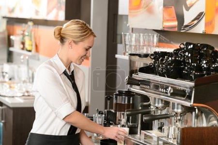 Waitress preparing hot beverage in coffee house