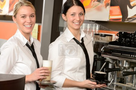 Photo for Cheerful waitresses serving hot coffee in bar in uniform - Royalty Free Image