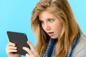Surprised young girl holding digital tablet