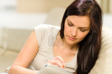 Young woman writing letter to copybook